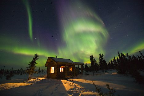 Northern Lights dance over a cabin in Fairbanks